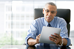 Professionally dressed African American man sitting at a desk, looking at a tablet.