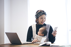 Asian mother in headwrap, holding a baby on her chest with a sling, looking at her phone with an open laptop on the table